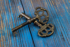 Two old keys on a wooden background Royalty Free Stock Image