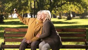 Two old ladies taking selfie on mobile phone sitting on bench in park technology. Stock photo royalty free stock images