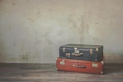 Old suitcases. Two old leather suitcases stand on the floor in an empty room Stock Photos
