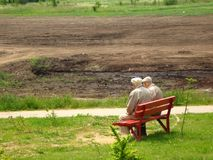 Two old man sitting on the bench. Two older man looking at deepening pond and levelling terrain stock photos