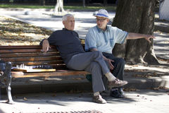 Two old man talking on a bench waiting for wanting to play a game of chess. Stock Image