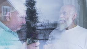Two old men drinking alcohol whiskey standing near the window at home. Caucasian old men neighbors friends enjoying time. Together indoors. Leisure of the stock footage