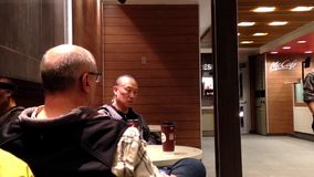 Two old men drinking coffee at mcdonalds stock video footage