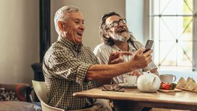 Two old men looking at old photographs together and laughing. Senior men looking at the old photographs to them in mobile phone and laughing. Two old men looking royalty free stock image