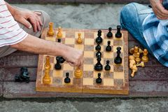 Two old men play chess. Two old men play old chess on a shabby board Royalty Free Stock Images