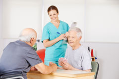 Two old men playing cards. In a nursing home with smiling nurse watching Royalty Free Stock Images