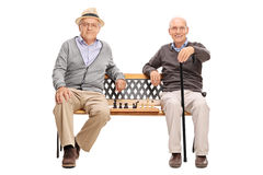 Two old men posing seated on a wooden bench Stock Photo
