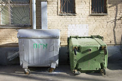 Two old metal dumpsters in the yard of residential building Stock Photo