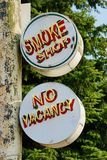 Two Old Metal Painted and Neon Smoke Shop and No Vacancy Signs. Outside an abandoned hotel smoke shop and no vacancy signs are hanging high up on a rusted metal Royalty Free Stock Photography