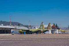 Two old military airplanes parked in the air strip waiting to be repaired out of the workshop Royalty Free Stock Image