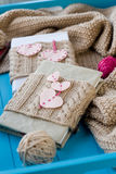 Two old pads in knitted cover with felt hearts lie next to the c Stock Photos