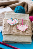 Two old pads in knitted cover with felt hearts Stock Images