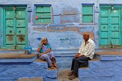 Two old people in front of their blue house Stock Image