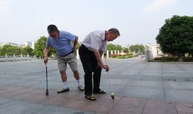 Two old people writing calligraphy on the ground. China has entered an aging society, in urban and rural areas, there are many elderly people together to Stock Photo