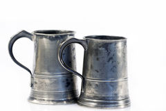 Two old quart pewter drinking jars. Pair of old and battered pewter ale jars quart size Royalty Free Stock Photos
