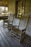 Two old rockers. Two rocking chairs on the front porch of an old home stock photo