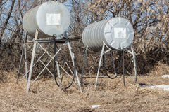 Two old round metal fuel and gas tanks with hose and nozzle Stock Photo