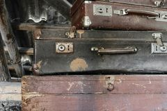 Two Old, Rusty, Dusty and Dirty Suitcases Lying on the Brown Chest. Two old, rusty, dusty and dirty brown and black suitcases lying on the brown chest in attic stock image
