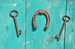 Two old rusty historical key and luck symbol horseshoe on  wall. Two antique rusty historical key and luck symbol horseshoe on wooden farm wall Stock Image