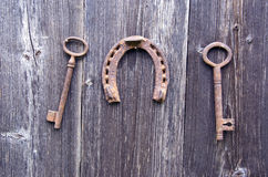 Two old rusty historical key and luck symbol horseshoe on wall Royalty Free Stock Photos