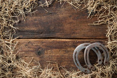 Two old rusty horseshoes with straw Royalty Free Stock Images