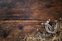 Two old rusty horseshoes with straw. On vintage wooden board royalty free stock images