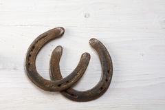 Two old rusty horseshoes on white painted wood, symbol for good Stock Images