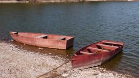 Old rusty metal boats chained on a river bank on sunny day