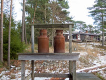 Two old rusty milk jug on a bench Stock Images