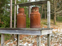 Two old rusty milk jug on a bench Royalty Free Stock Photography