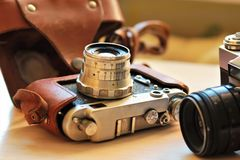 Two old school vintage photo cameras on light brown table. One in brown retro leather case holder royalty free stock image