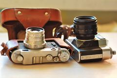Two old school vintage photo cameras on light brown table. One in brown retro leather case holder. Blurred background Royalty Free Stock Photos