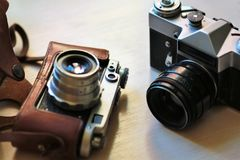 Two old school vintage photo cameras on light brown table. One in brown retro leather case holder Royalty Free Stock Photography
