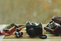 Two old school vintage photo cameras and scattered films on light brown table. One in brown retro leather case holder. Blurred. Autumn background Royalty Free Stock Photos