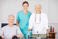 Two old senior people in nursing home. With a geriatric nurse Royalty Free Stock Images