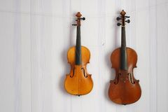 Two old shabby broken violins of a different size for restoration hanging on the wall with copy space for your text royalty free stock image