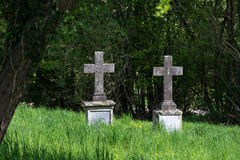 Two old  stone crosses as tombstones in an overgrown cemetery Stock Photography
