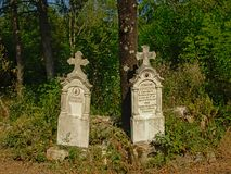 Two old Stone grave monuments in the Romanian countryside. Two old worn stone gravetombs in between trees and shrubs in the Transylvanian countryside, Romania stock images
