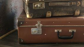 Two old suitcases are on the shelf. Camera movement stock footage