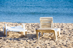 Two old sunloungers on tunisian beach Royalty Free Stock Photos