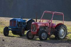 Two old tractors, blue tractor and red tractor in Iceland royalty free stock image