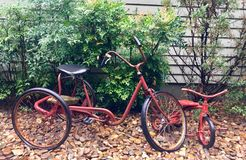 Two old Tricycles in a Yard. An old adult`s bike and a children`s bike parked in front of a house royalty free stock image