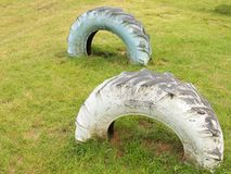 Two old truck tires in ground of playground. Stock Photography