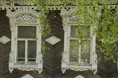 Two old village windows. Two ancient Russian wood windows with platbands Stock Image