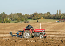 Two old vintage red tractors ploughing Stock Photos