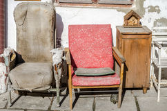 Two old vintage retro broken reclining seats porvanoy cloth on a background of white whitewashed wall with cracks and old bedside Royalty Free Stock Image