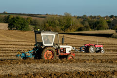 Two old vintage  tractors ploughing Stock Photography