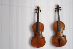 Two old violins of the same size hanging on the wall with copy space for your text royalty free stock photos