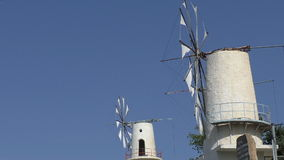 Two old white windmills working. Low angle side view of two old traditional white windmills against blue sky still working stock video