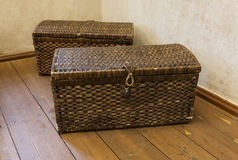 Two old wicker from cane chests standing in the room corner Stock Photography